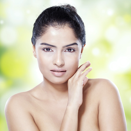 smooth hair: Young indian woman with black hair and clean skin, looking at the camera against bokeh background Stock Photo