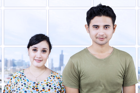 Happy couple looking at camera in apartment with cityscape