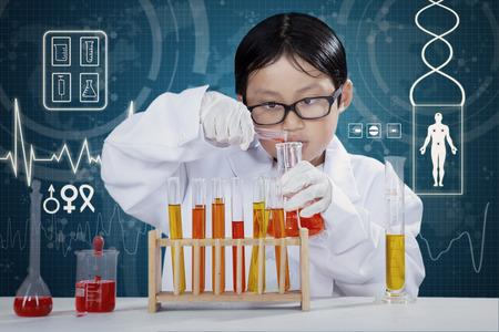 niños estudiando: Retrato de la pequeña capa del muchacho de vestir y hacer experimentos en el laboratorio con el líquido químico