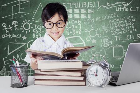 escuela primaria: La pequeña colegiala lectura de libros en el aula con el reloj de alarma, ordenador portátil y papel en el vector