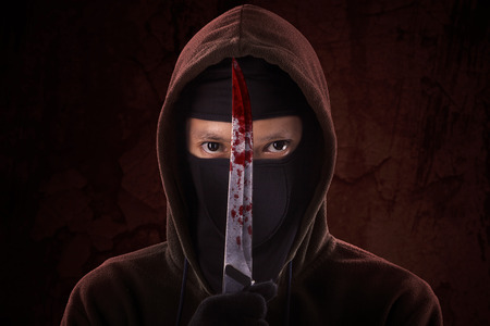 holding a knife: A frightening man holding bloody knife