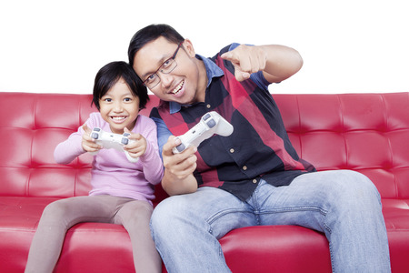 playstation: Portrait of happy little girl sitting on the sofa while playing video game with her father, isolated on white