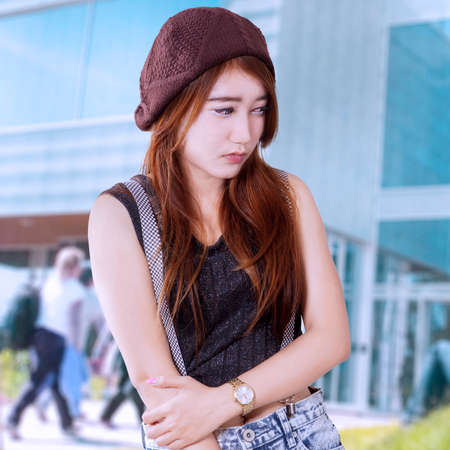 long depression: Lonely female student standing in front of school building with sad expression Stock Photo