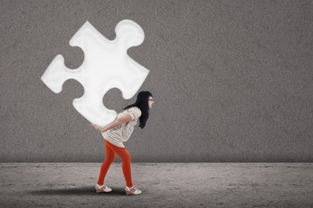 bring: Asian female student bring puzzle on grey background
