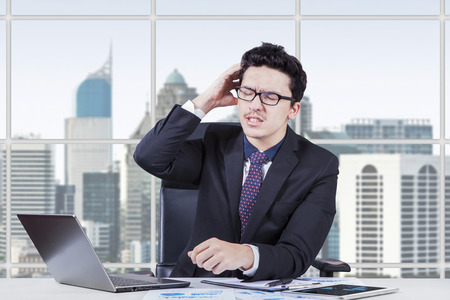 worrying: Young businessman worrying his job while scratching his head in the office