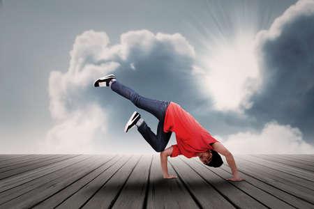 bailarin hombre: Energic bailar muchacho asi�tico bajo las nubes Foto de archivo