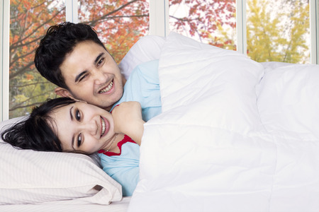 joking: Attractive couple joking and laughing on bedroom with autumn background on the window