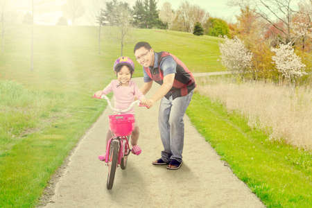 helps: Portrait of young father helps his daughter riding a bicycle on the park Stock Photo