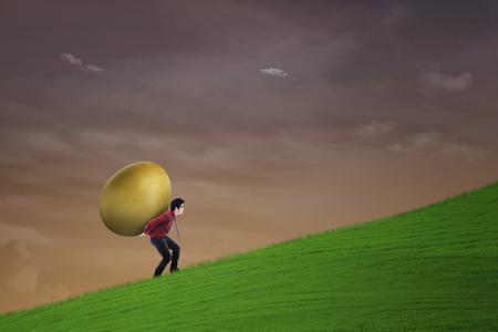 gold egg: Businessman is carrying gold egg under sunset sky