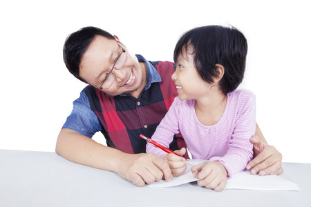 white back: Portrait of male teacher smiling at a little girl while helping her to study, isolated on white background