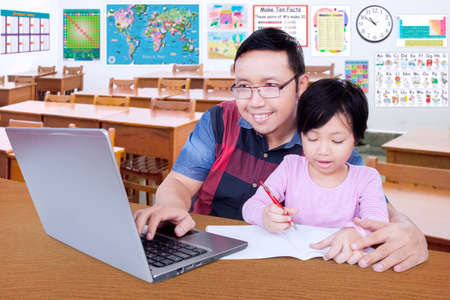 asian adult: Female elementary school student write on the book in the classroom while her teacher using laptop