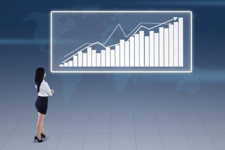 upward graph: Businesswoman looking at bar chart on blue background