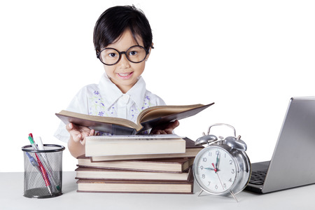 science education: Lovely kindergarten student reading books on the table while wearing glasses and smiling at the camera
