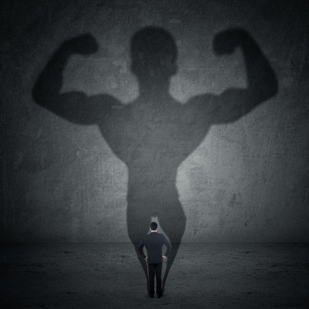 metaphor: Business man casting a shadow of an athlete - business and career strength concept