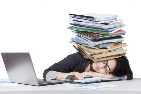 Portrait of overworked female worker sleeping on desk with paperwork over head, isolated on white Stock Photo