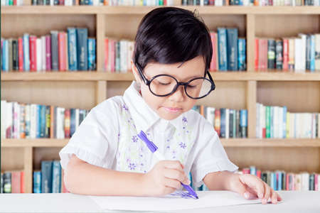 library book: Portrait of little girl sitting in the library while drawing on a paper with a marker and wearing glasses