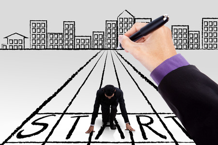 start line: Businessman kneeling on a start line with a hand drawing the line and a city