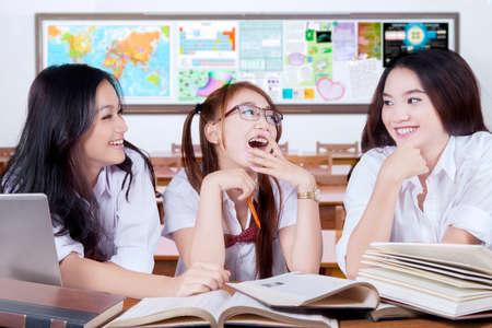amigas conversando: Retrato de tres estudiantes adolescentes alegres estudiar y riendo juntos en el aula Foto de archivo