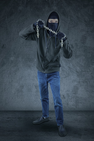 Male murderer wearing black jacket and mask, showing a chain to kill Stock Photo