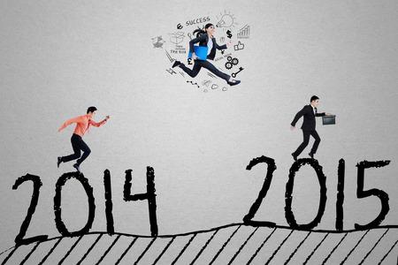 jovenes empresarios: Jóvenes empresarios corren por encima de número 2.014 a 2.015 y compiten para conseguir el número 2.015, que simboliza la competencia empresarial para el éxito en el futuro