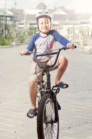 kids outside: Portrait of cute boy riding a bicycle while wearing helmet on the road Stock Photo