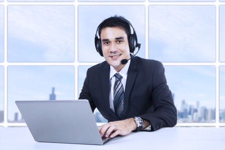 ultrabook: Portrait of happy smiling customer support phone operator in headset at office
