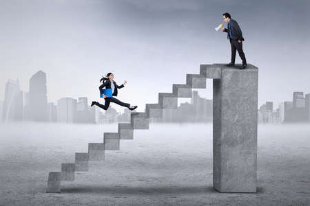 finance director: Young female employee runs hurry on the stair to meet with her bos on the bar Stock Photo