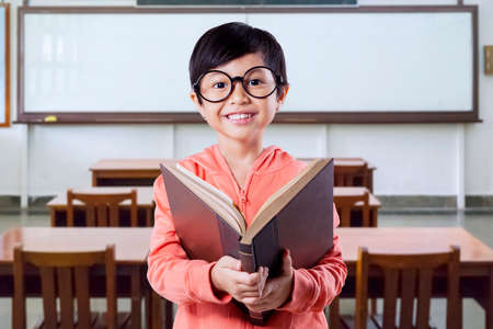 joy of reading: Sweet little girl standing in the classroom while wearing glasses and holding a book, smiling at the camera