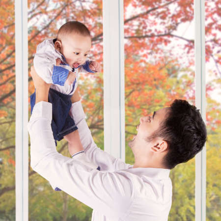 asian toddler: Cheerful young father standing near the window while lifting up his baby at home
