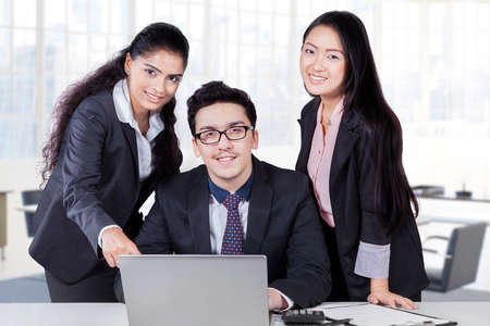 multi racial: Portrait of multi racial businesspeople working with laptop in office and looking at the camera