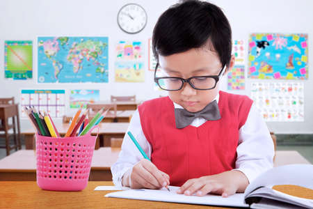 indian student: Portrait of male elementary school student wearing glasses in the class while drawing on the paper Stock Photo