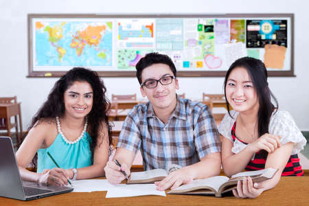 high tech: Group of three mixed race student studying together in the class and smiling at the camera Stock Photo