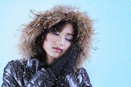 fur hood: Pretty woman wearing comfortable winter jacket with fur hood in front of blue background