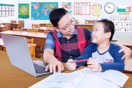 guiding: Young teacher talking with his student while guiding him to study with books and laptop in the classroom Stock Photo