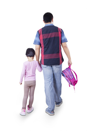 walking: Rear view of young father walking to school with his daughter while carrying backpack, isolated on white background