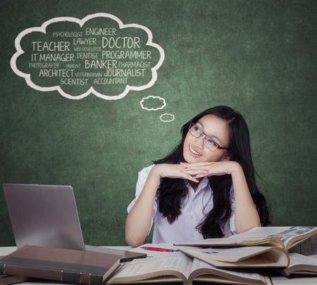 Retrato de una hermosa estudiante de secundaria sentado en el salón de clases mientras imaginar futuros trabajos