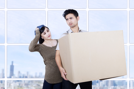 relationship problem: Confused couple bring box at apartment with cityscape