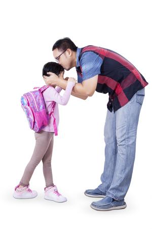 ir al colegio: El concepto de volver a la escuela con un padre joven que besa a su hija antes de ir a la escuela. Aislado en el fondo blanco