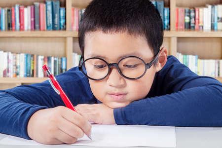 escribiendo: Hombre estudiante de escuela primaria escribir en el papel con una pluma en la biblioteca Foto de archivo