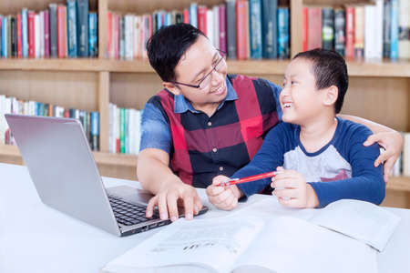 adult student: Elementary school student talking with his teacher while studying in the library