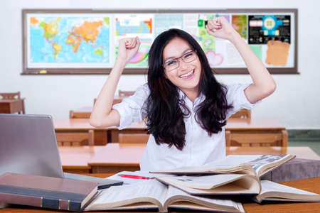 to raise: Portrait of beautiful female high school student with black hair, celebrating back to school and raise hands in the classroom