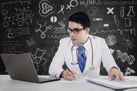 healthier: Male doctor writes medical reports at the desk