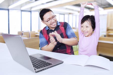 Portrait de l'élève de l'école primaire attrayant célébrant son succès dans la salle de classe et son professeur donnant des applaudissements Banque d'images - 45504353