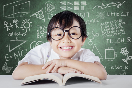 kid book: Portrait of lovely female kindergarten school student wearing glasses and smiling at the camera in the classroom