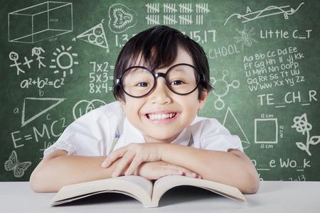 kinder: Retrato de la hermosa estudiante de kindergarten femenino que lleva gafas y sonriendo a la c�mara en el aula