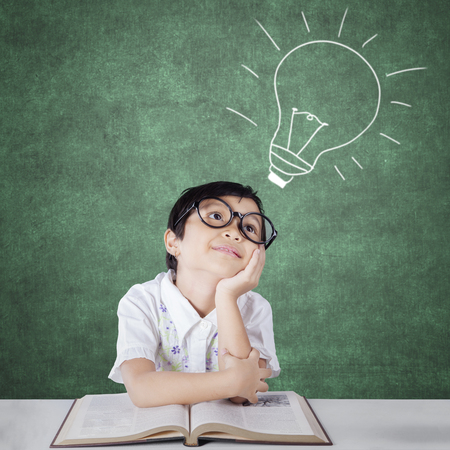 imagining: Portrait of female primary school student sitting in the classroom while wearing eyeglasses and imagining a light bulb