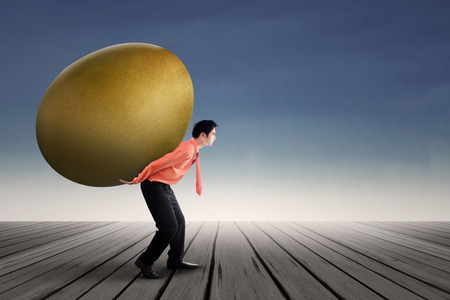 golden egg: Young businessman is carrying a golden egg investment on his back Stock Photo