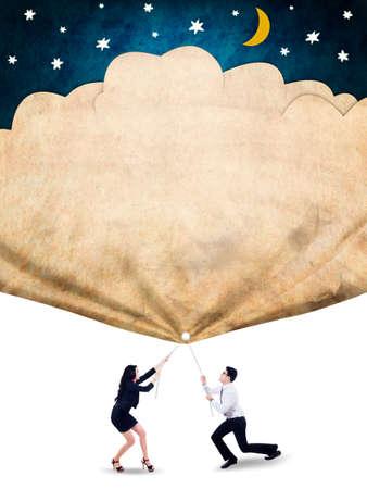jonge ondernemers: Twee jonge ondernemers werken samen om een banner met sterren en de maan te trekken, als symbool van hun hoop op succes
