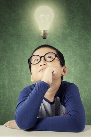 Photo of a thoughtful primary school student thinks idea under a bright light bulb in the class Stock Photo