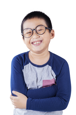 folded hands: Portrait of a primary school student with casual clothes and glasses, smiling at the camera in the studio, isolated on white